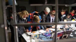 Interessierte Besucher begutachten die Ausstellung zur Astronomie in der Bibliothek